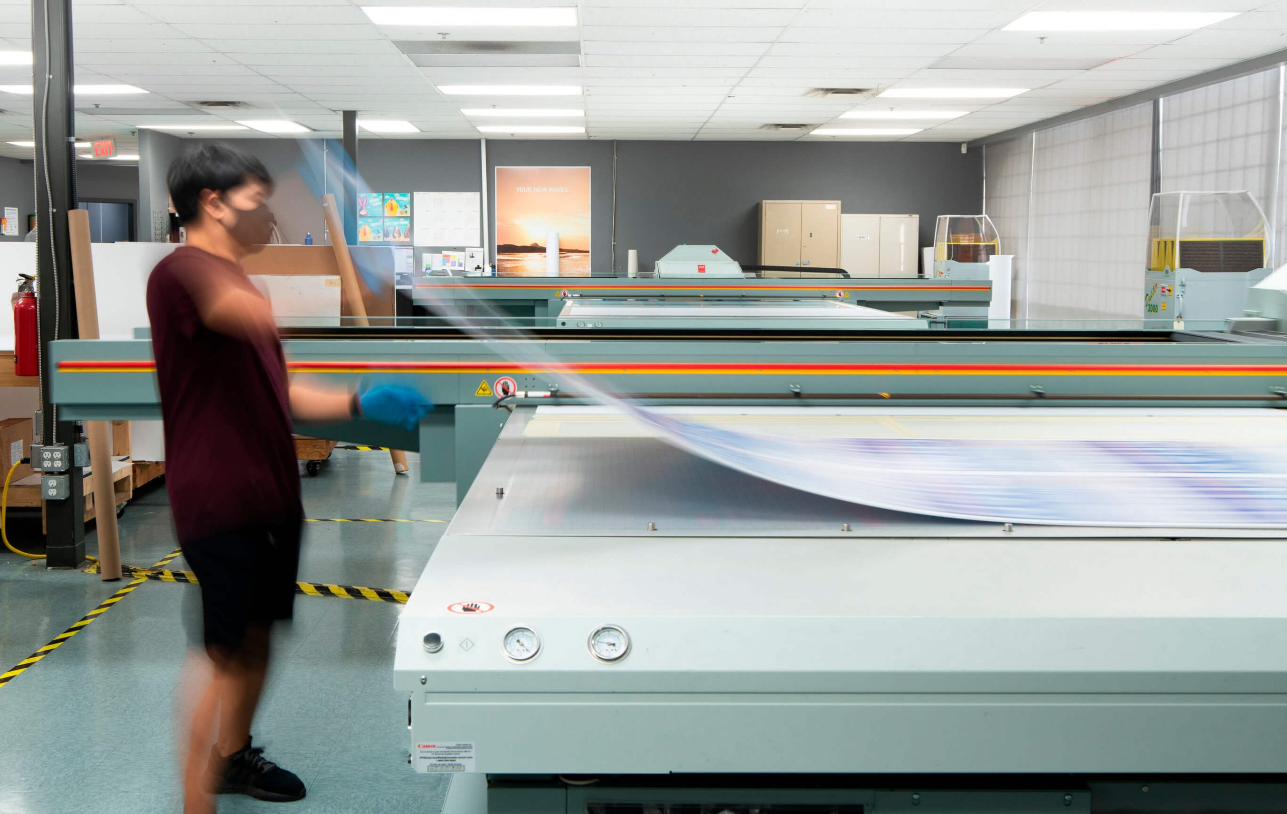 UV flatbed printing operator laying a sheet of media on the press