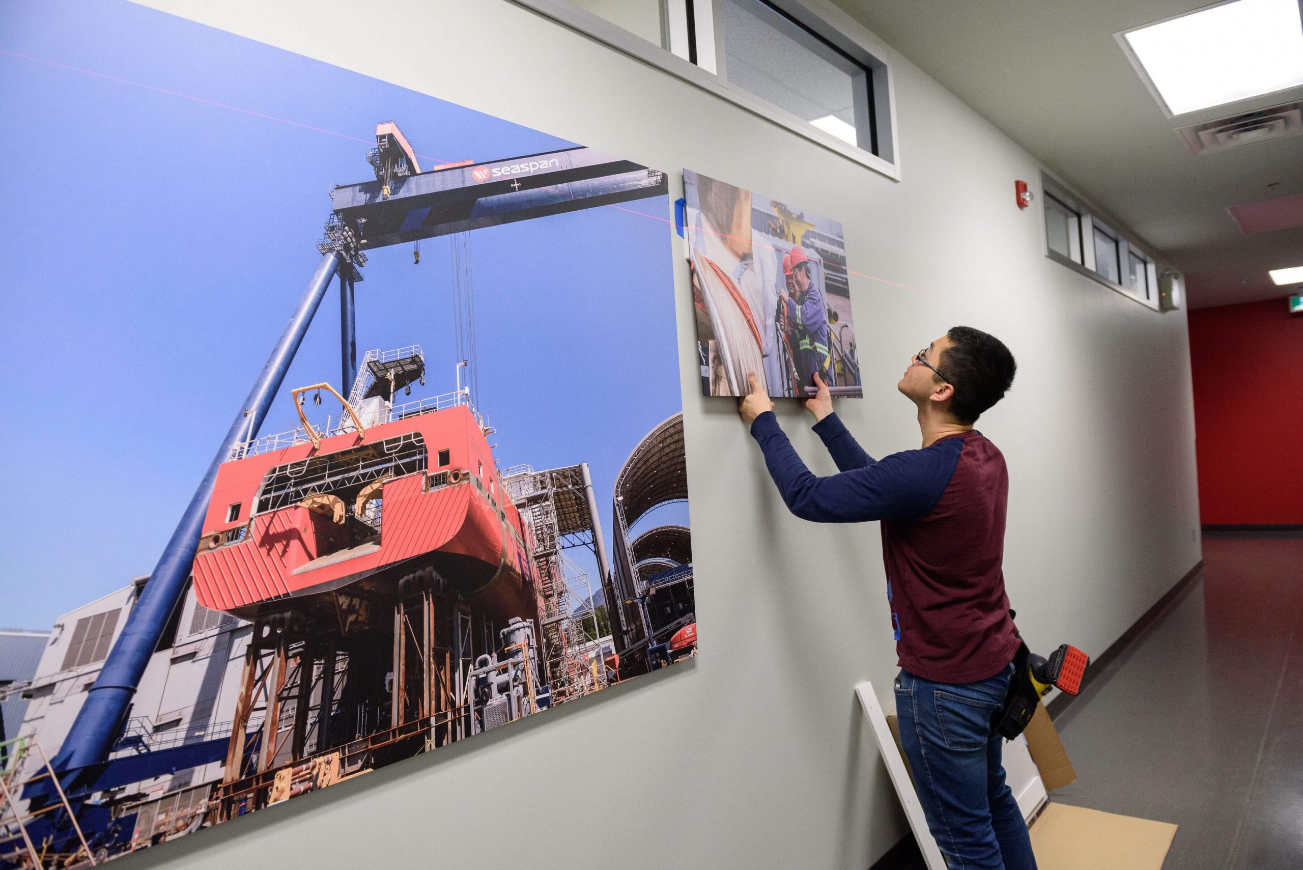 Man installing a printed image on a wall