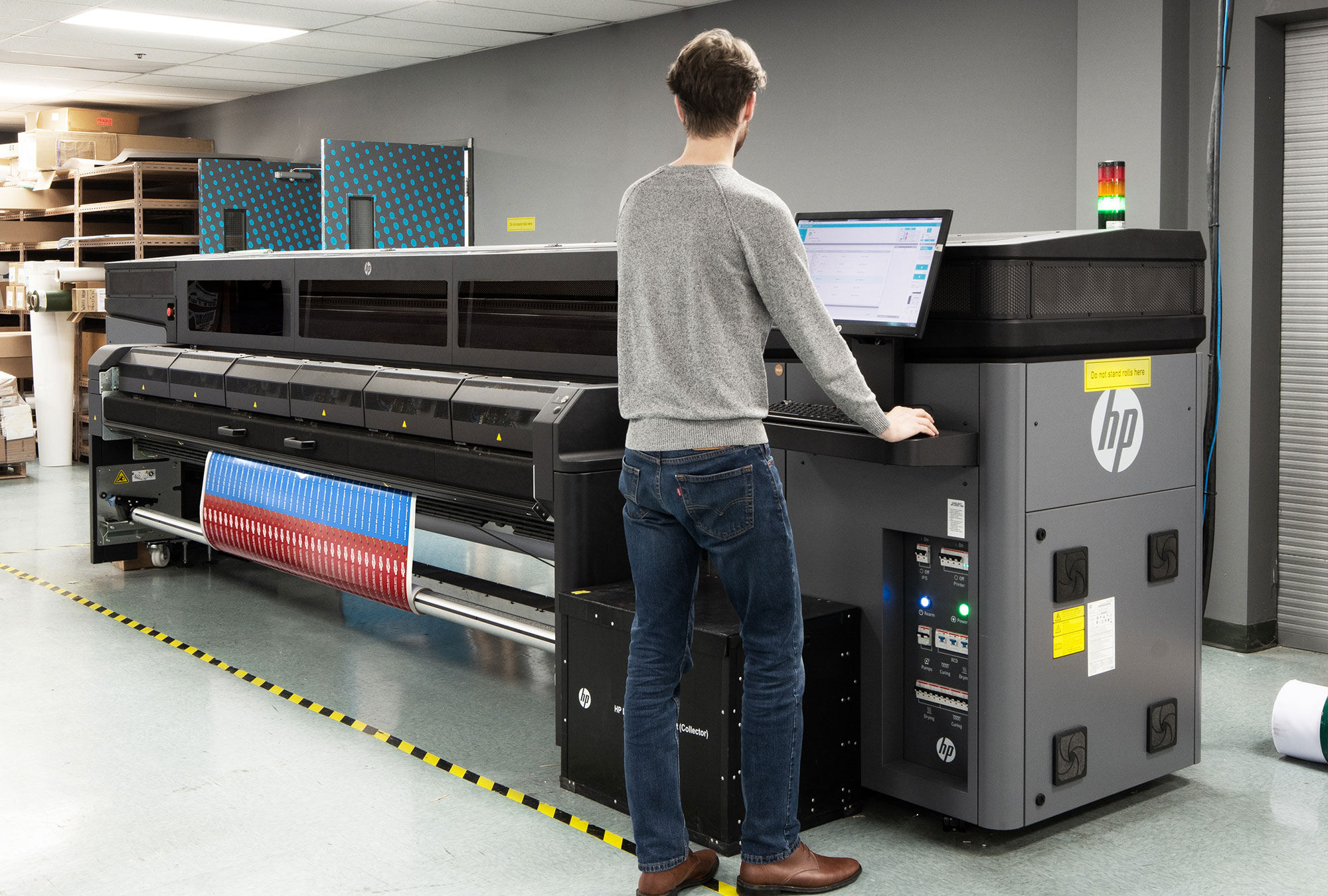 Man operating HP latex roll to roll printer