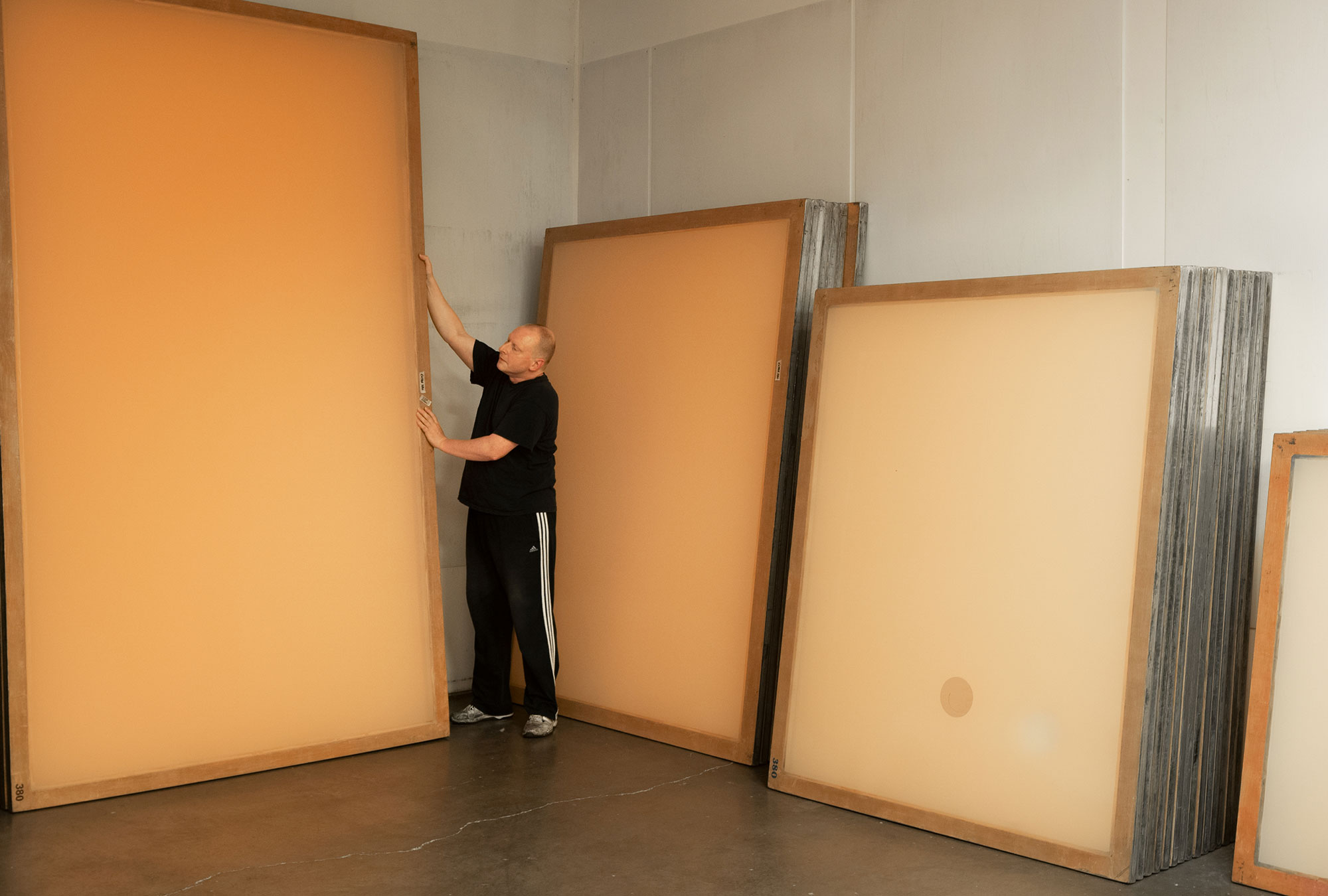 Screen press operator standing next to screens larger than him